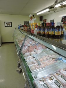 Indoor view of butcher shop, spices, sauces, counter